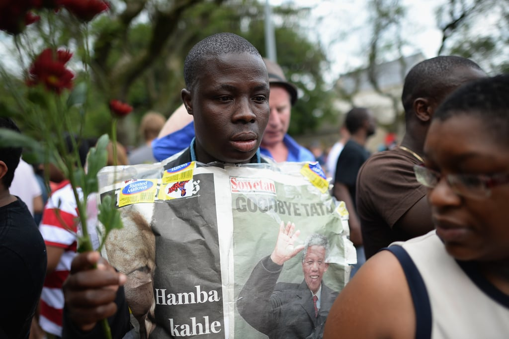 A man held up the newspaper depicting Nelson Mandela during the public memorial.