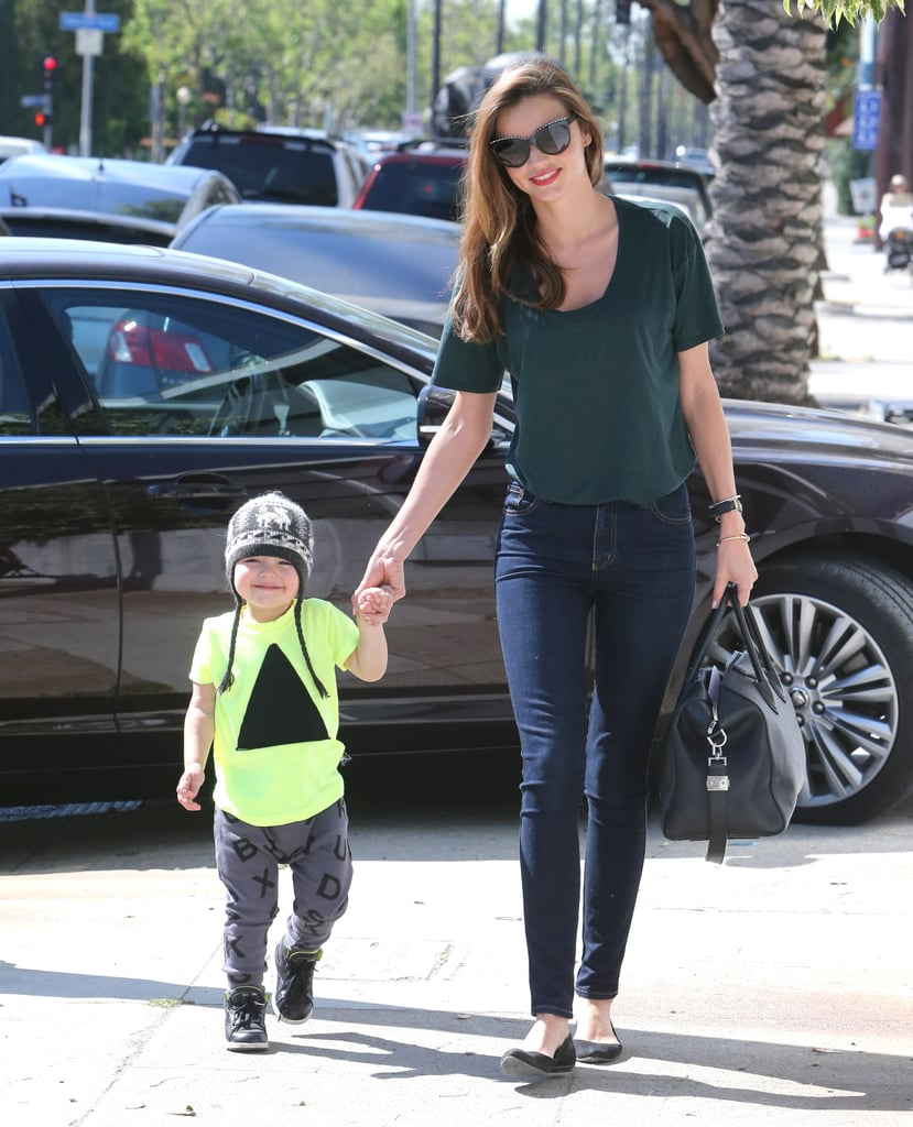Miranda Kerr made jeans and a t-shirt look chicer than your average casual combo by sticking to dark, skinny denim and finishing with a luxe satchel and classic ballet flats. Like mom, like son — Flynn looked adorable in a beanie and a neon tee at her side.