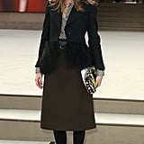 At the Burberry Prorsum show in London, Olivia took ladylike-chic to new heights in a printed blouse, a knee-length olive skirt, and a fur-trim Armani blazer. Her neon Fendi clutch injected the perfect dash of colour.
