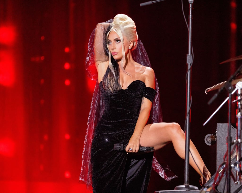 """Lady Gaga is practically the face of Old Hollywood glamour, so her recent looks during a performance celebrating the launch of Love For Sale, her new album with Tony Bennett, may come as no surprise. Yet they were extra special, as they were designed by her own sister, Natali Germanotta, and her new brand Topo Studio.  The talented artist first entered the stage on Sept. 30 wearing a sheer, crystal-embellished number with feathers galore, then changed into a sleek velvet off-the-shoulder gown with glitter details. Both dresses featured leg slits so high, they offered a glimpse of Gaga's unicorn tattoo paired with the words """"Born This Way"""" on her thigh.   Gaga shared photos from the performance to her Instagram on Thursday, writing, """"It was a joy to sing for you today, thank you for watching online or joining in person, and for coming together with me to celebrate 'Love For Sale'! @itstonybennett and I are so excited for you to hear our album 🎷🎺!"""" She added, """"And thank you to my talented sister @germ_aphobenotta @topostudiony for designing my beautiful costumes for the show! ❤️"""" Ahead, get a closer look at the singer's sparkly custom looks.      Related:                                                                                                           I'm Surprised the Billowing Sleeves on Lady Gaga's Velvet Gown Didn't Send Her Flying Away"""