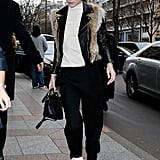 Kendall Jenner stayed comfortable on the streets of Paris in white sneaks, loose fitted pants, and a black leather jacket. She finished off the look with a touch of fur and shades.