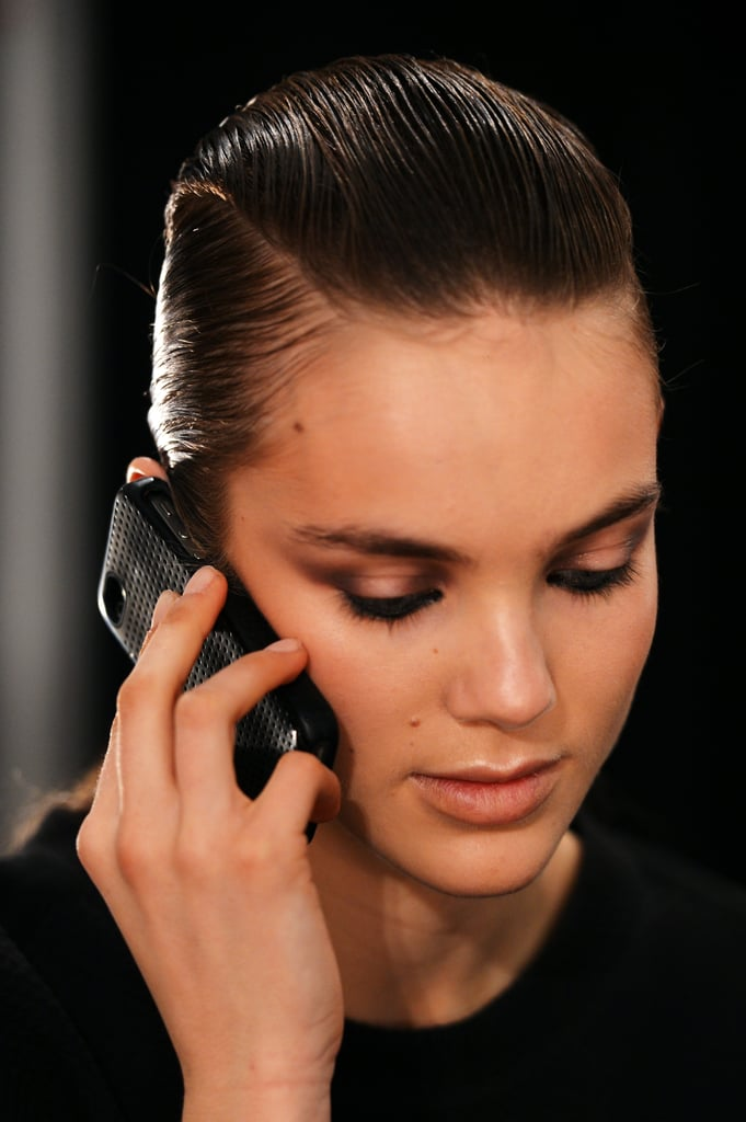 """Makeup artist Max Delorme used both matte and shimmer products to create a look that balanced strong and soft notes. """"What I like about makeup in this moment is when you mix texture and color,"""" he said. """"We tried to find a way you can be strong, but still feminine in a way."""" On the eyes, he enlisted the models to help smudge a shimmer shadow on the outer and inner corners. He then lined the inner eye with a mix of MAC Feline and Ebony eyeliner."""