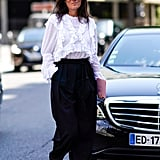 Emmanuelle Alt's Parisian chic take on high-waisted pants relies on a ruffled white blouse and bohemian sandals.