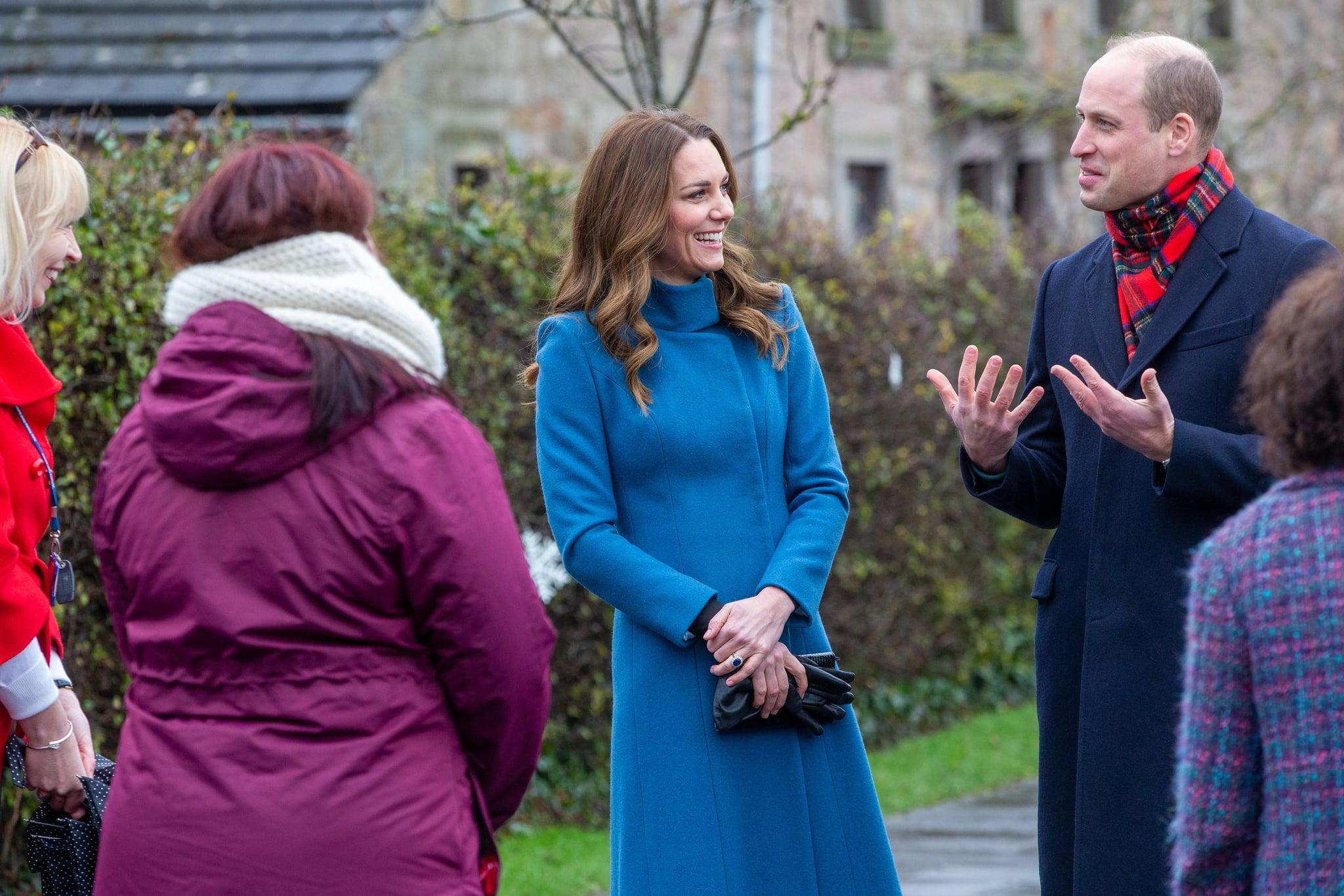Kate sorri enquanto olha para William que gesticula ao ar livre. Eles ainda estão com as roupas dos compromissos na Escócia. Há três professoras de costas.