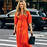 Laura Lajiness looks casual and comfortable in a tomato red pouf-sleeve maxi and flat black sandals.