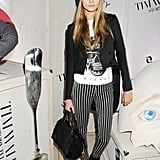 Cara Delevingne offset a rocker-chick ensemble (how much do you love her railroad-stripe jeans?) with a preppier looking monogrammed beanie.