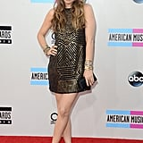 Alicia Silverstone put her gams on display in a gold, metallic mini and classic pumps. We are loving her loose curls and sexy smolder.
