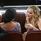 Jennifer Lawrence, wine in hand, chatted with Salma Hayek.