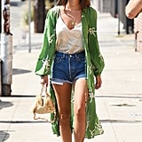 Emily Ratajkowski layered up her classic denim shorts with a printed kimono jacket and silky tank. Her outfit gets the fashion-girl treatment via white-trimmed shades and a Carolina Santo Domingo woven bag.