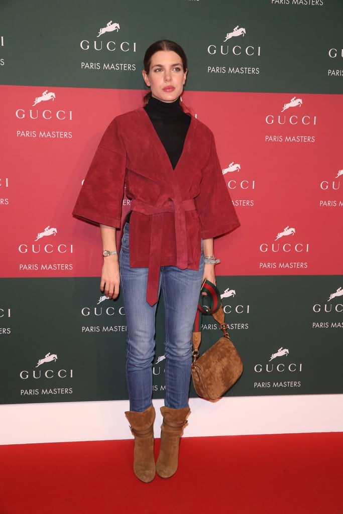 For a day at the Paris Masters in December 2014, Charlotte Casiraghi wore a casual outfit with jeans, a black turtleneck, red suede kimono, and suede boots.