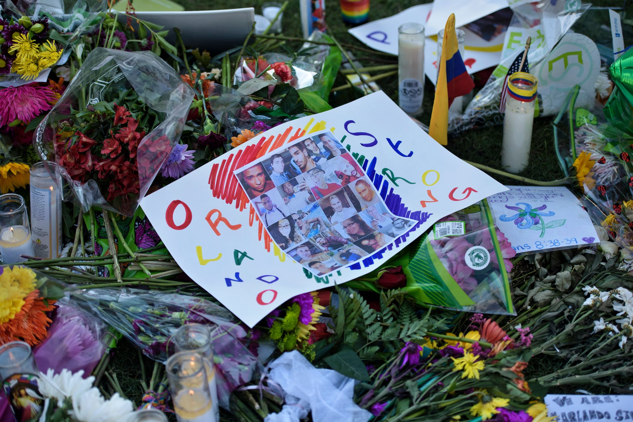 Photos and flowers are seen at a memorial at the Dr. Phillips Center for the Performing Arts to honor the Pulse nightclub mass shooting victims June 14, 2016 in Orlando, Florida.The gunman who launched the worst terror attack on US soil since 9/11 at a gay nightclub in Orlando was radicalized by Islamist propaganda, officials said, amid reports he was a club regular. Lone gunman Omar Mateen killed 49 and wounded another 53 before he was killed when police stormed the Pulse, one of Orlando's most prominent gay venues, early Sunday. / AFP / Brendan Smialowski        (Photo credit should read BRENDAN SMIALOWSKI/AFP via Getty Images)