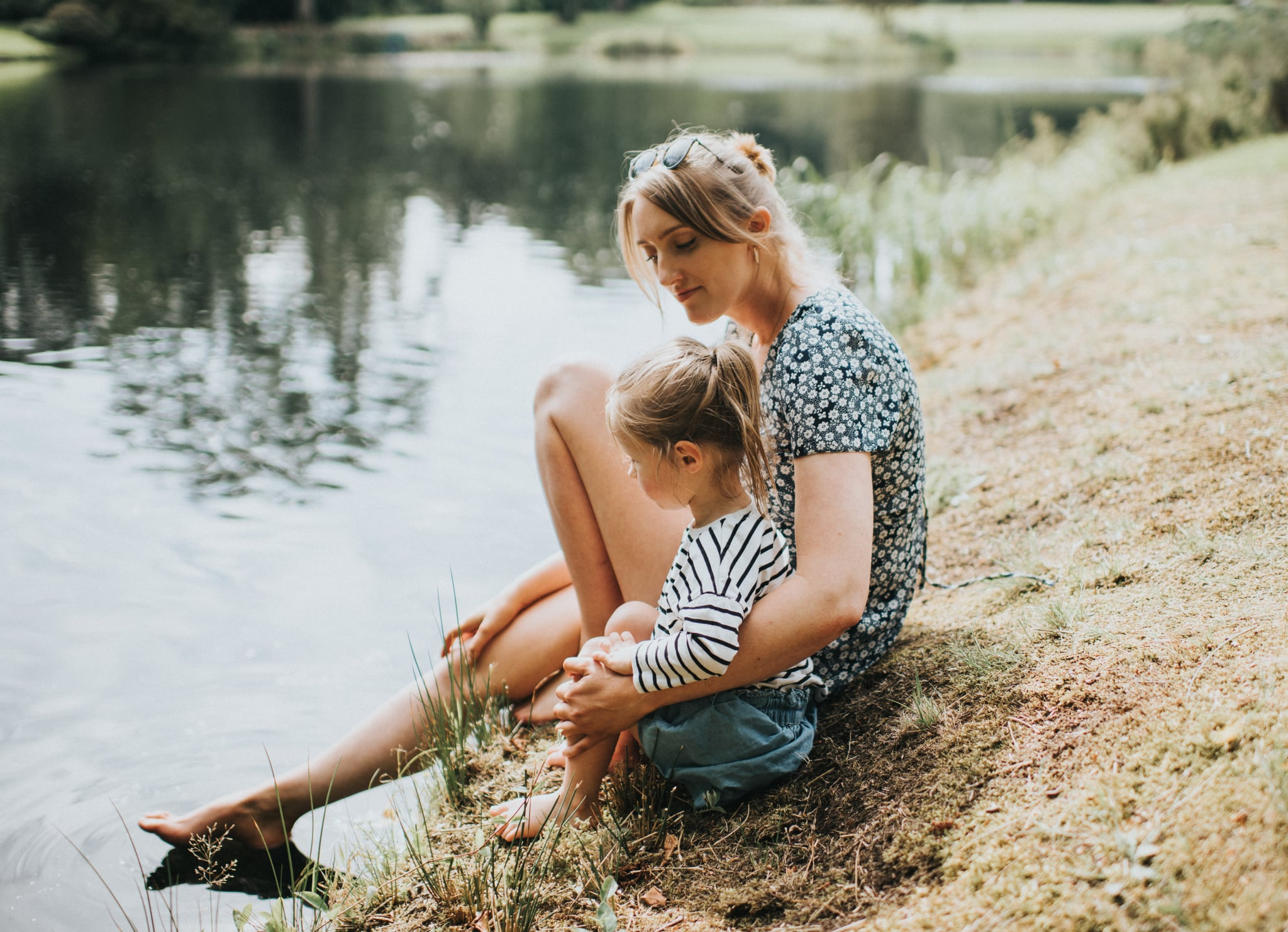 Adult and child together at the edge of a lake.