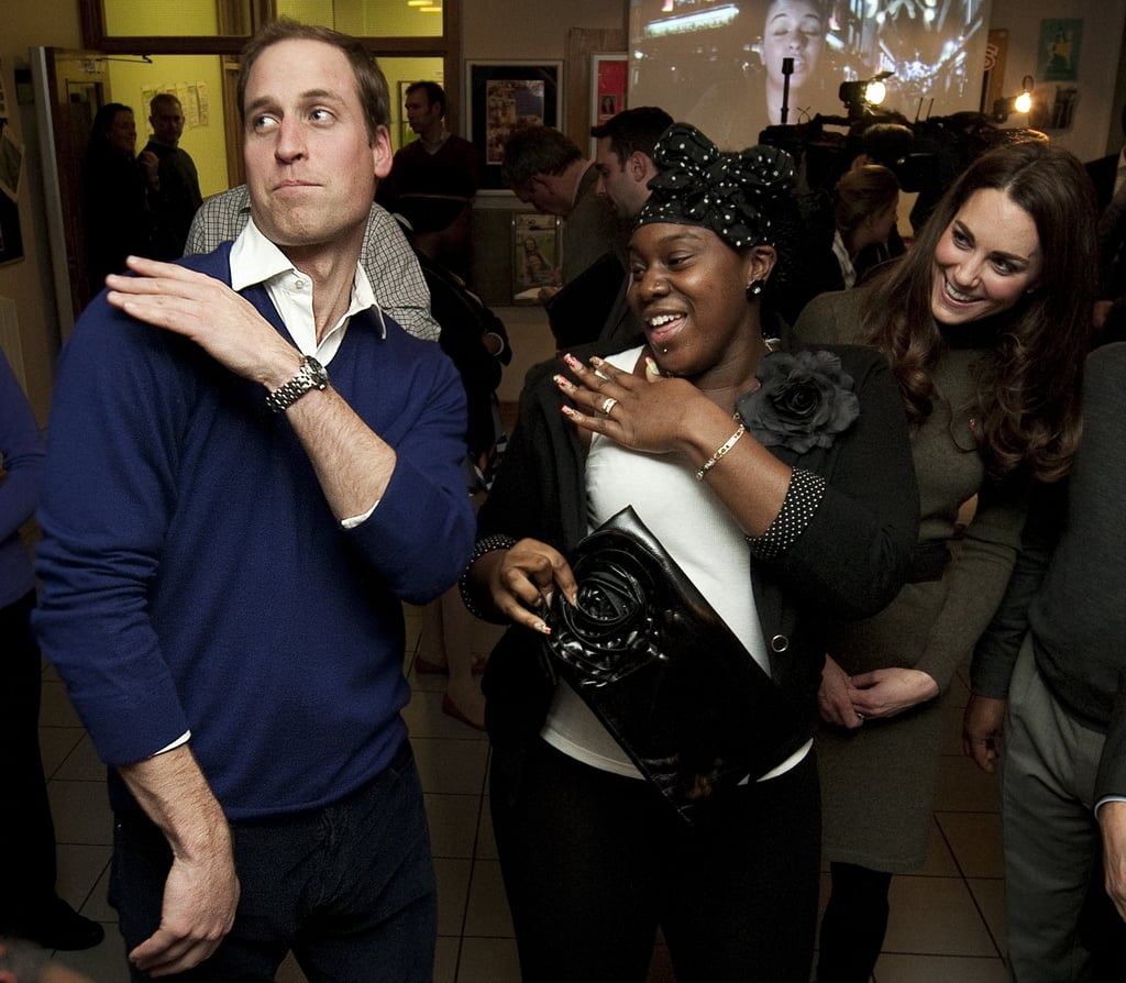 """Prince William and Kate Middleton let loose during their visit to the Centrepoint charity in London! The couple took part in a cooking class, where they made cookies and mince pies, then watched a production of """"Centrepoint's Got Talent."""" William and Kate weren't just onlookers, since he got in on the action —William teamed up with one of the young people associated with the organisation to do the """"brush some dirt of your shoulder"""" dance. His partner was 18-year-old Vanessa Boateng, who apparently instructed William, """"You dust your shoulders off twice."""""""