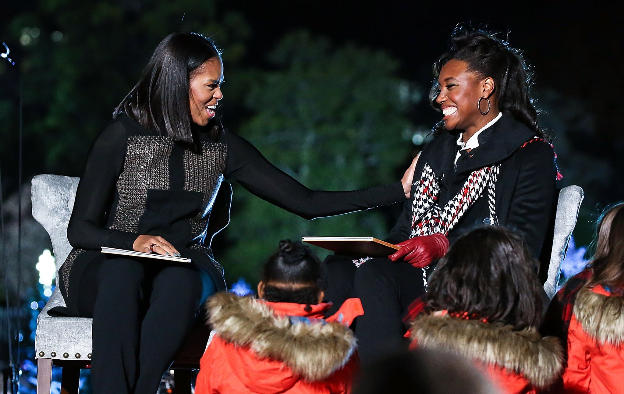WASHINGTON, DC - DECEMBER 01:  First Lady Michelle Obama (L) and Olympic medal winner Simone Manuel read