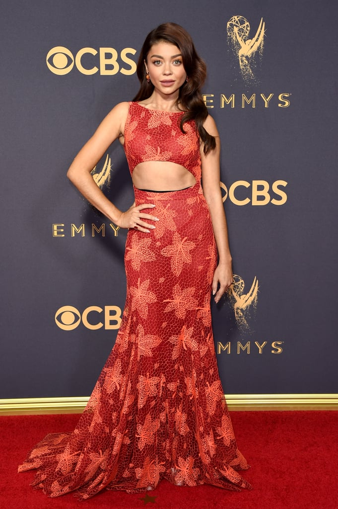 Sarah Hyland is no stranger to the Emmys red carpet, but on Sunday night, she did it in a way she's never done before. The Modern Family actress wore a stunning Zac Posen gown from his 2018 Resort collection, and it was the perfect reminder that just because Summer is technically almost over, sexiness has no end date. Sarah's abs popped through the leaf-adorned lace gown as she lit the red carpet ablaze with her red-hot look. Read on to see Sarah's full look, and then check out all the gorgeous red carpet fashion at the 2017 Emmy Awards.