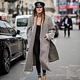 Keep Things Chic and Simple With a Black Cap, Strappy Sandals, and a Long Checked Coat