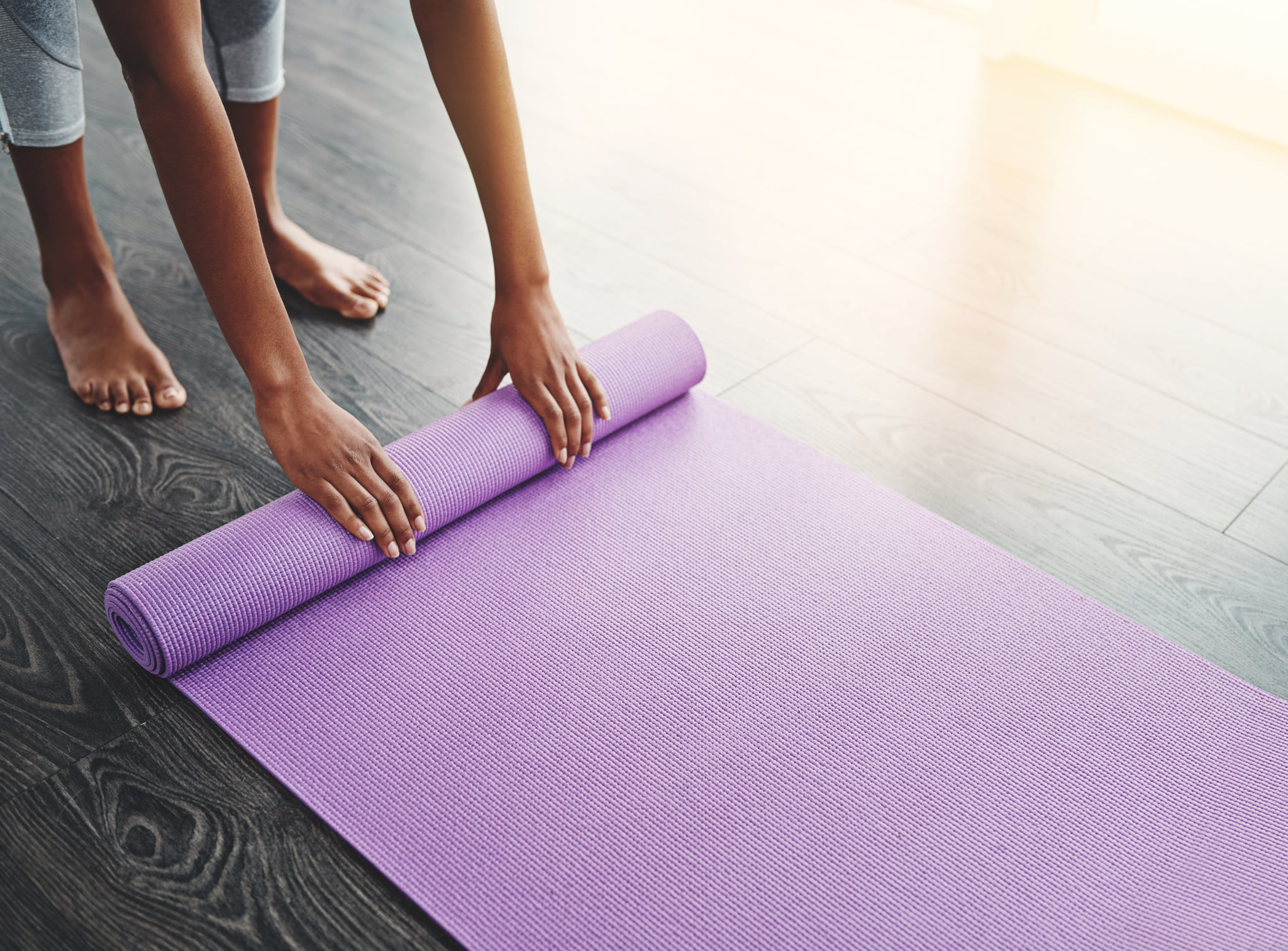 Cropped shot of an unrecognizable woman rolling up her yoga mat
