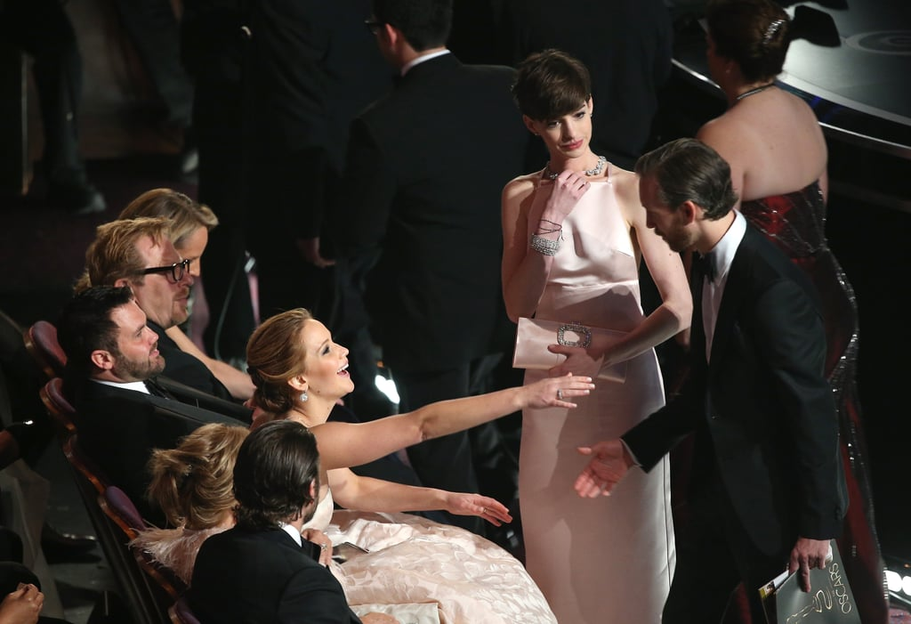 Jennifer Lawrence with Anne Hathaway and Adam Shulman at the Oscars 2013.