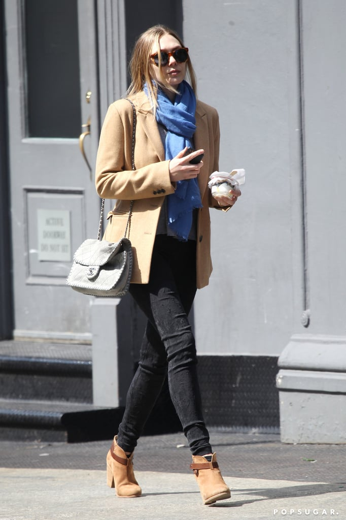 Elizabeth Olsen paired her beige coat with a bright blue scarf.