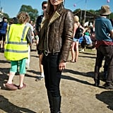Kate Moss maintained her cool-girl reputation in a shearling leather jacket, black skinny denim, black leather boots, and dramatic cat-eye sunglasses at the 2013 Glastonbury Festival.