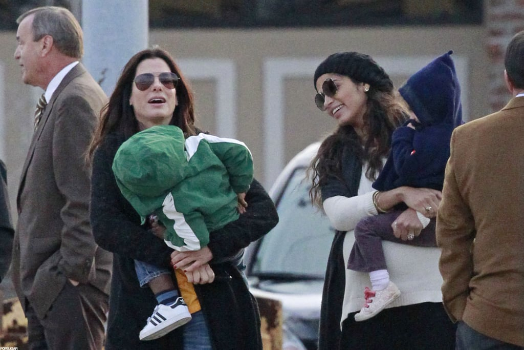 Sandra Bullock and Camila Alves had a laugh together as they held their children in New Orleans.