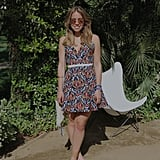 Popsugar Fashion Editorial Assistant Sarah Wasilak accessorized a playfully printed babydoll dress with a cream fringe bag, neutral Dolce Vita sandals, and mirrored Ray-Ban sunglasses.