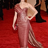 Nora Zehetner walked the carpet in a printed metallic one-shoulder Marchesa gown with a matching red clutch and studded Edmundo Castillo sandals.