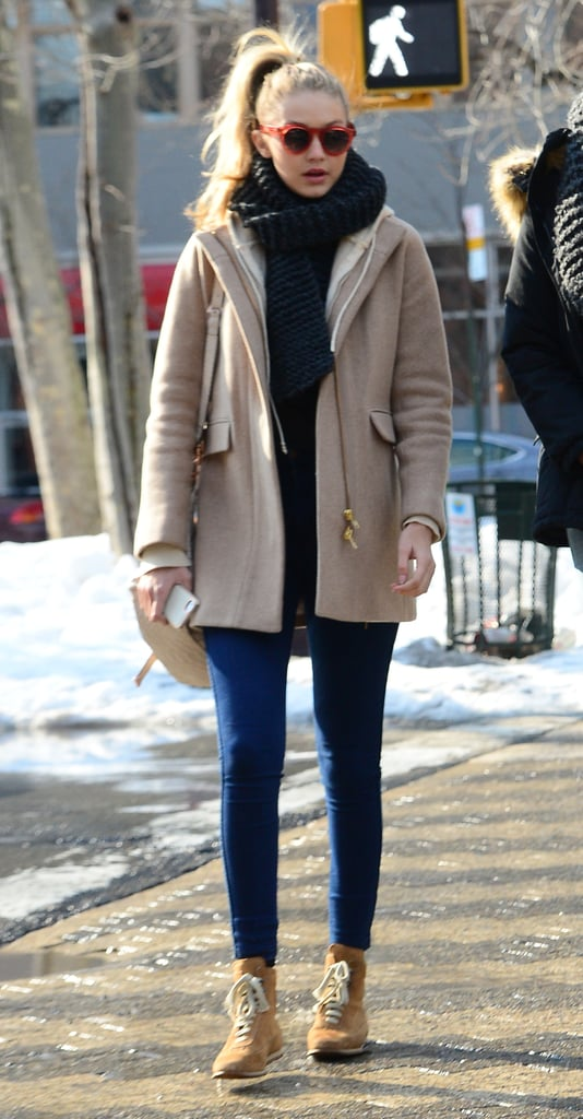 Wearing skinny jeans with a beige coat, booties, and a scarf.