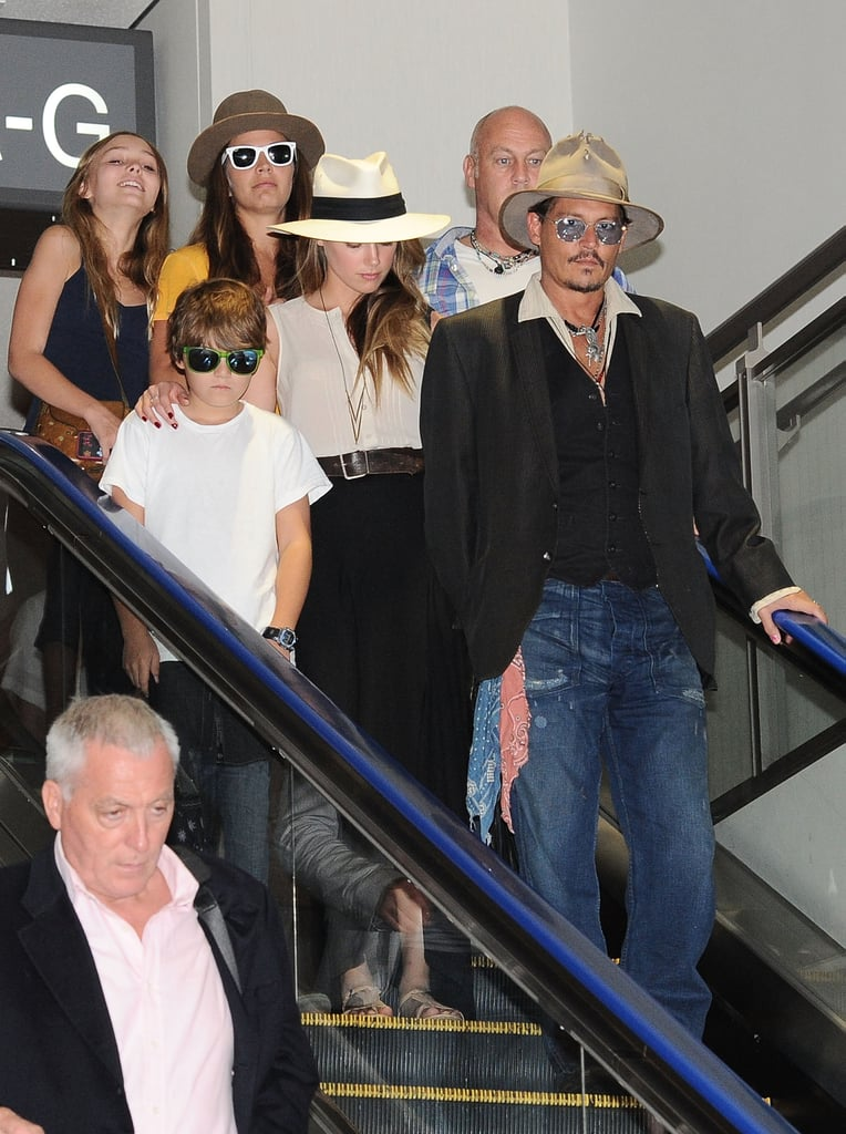 Amber Heard helped Johnny Depp with his two kids, Lily-Rose and Jack, when the whole family left Tokyo today. She put her arm around Jack as the family descended down an escalator at the airport. She was by his side earlier this week when she was spotted walking with Johnny's children when the family landed in Japan. Johnny was in Asia to promote his newest film, The Lone Ranger, which hit theaters in the States back in June. This isn't the first time that Amber has joined Johnny on the press trail, as the couple showed PDA after a screening of his latest flick in Moscow. However, this was the first time that Amber has been seen out with his children, who divide their time between Johnny and their mother, Vanessa Paradis, in France.