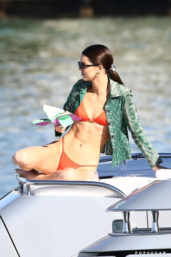 The longer Kendall Jenner vacations in Miami, the more my warm-weather envy increases. The 24-year-old model has spent the past few days enjoying the sea and sunshine while in town for Art Basel. She was recently seen spending some downtime on a boat wearing a Sommer Swim bikini and reading a book — although, it feels like I'm the one who should do some studying up after seeing this chic Summer style right before Winter.  Kendall brought a bunch of sexy selections along for this trip, including a barely there python-print two-piece and a hot-pink minidress that she wore for dinner with fellow model Joan Smalls. She used a patterned green button-down as a cover-up for her eye-catching orange bikini and tied the look together with gold earrings and a pair of rectangular shades. Keep reading to see more of Kendall's look, and to shop her exact suit.       Related:                                                                                                           Kendall Jenner and Gigi Hadid Set the Tone For 2020 With Their Matching Street Style