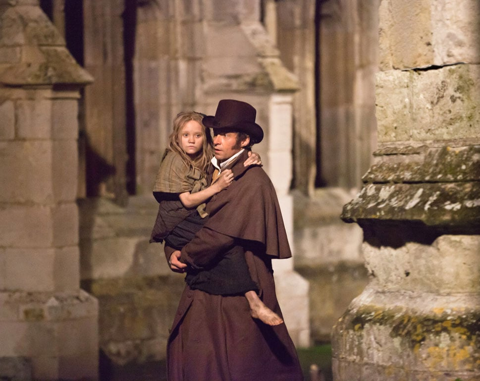 Hugh Jackman as Jean Valjean and Isabelle Allen as young Cosette in Les Misérables.