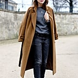 Street-cool pieces like buckled boots and a beanie got a sophisticated counter in this attendee's camel coat.