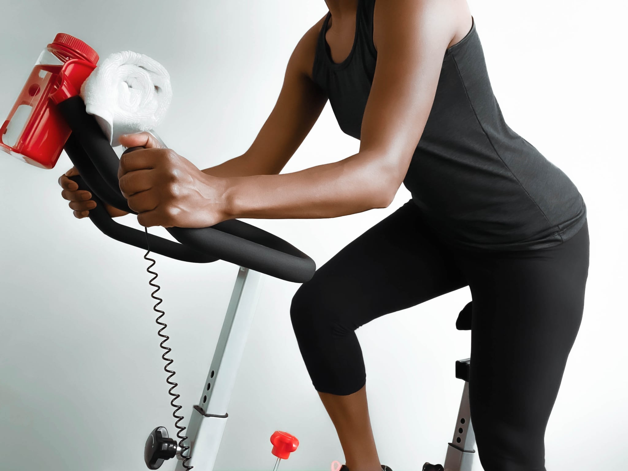 Close-up of unrecognizable black woman cycling at home on exercise bike
