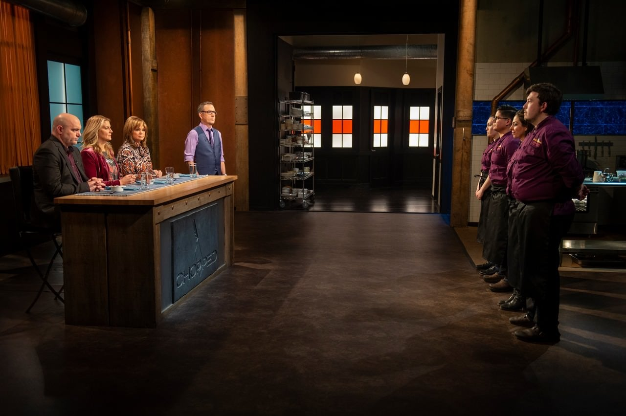 Host Ted Allen with judges Valerie Bertinelli, Chris Santos, and Amanda Freitag and contestants Aurora Wold, Ivan Marquez, Sandra Hakim, and Robert Gonzalez during round 1 tasting and judging during the Chocolate Part 4 of the Desserts Tournament, as seen on Chopped, Season 43.