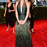 Kirsten Dunst showed off a bit of cleavage in a plunging Louis Vuitton halter gown with a fun feathered skirt.