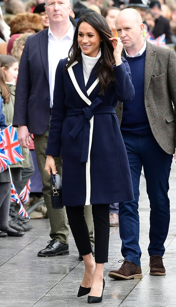 Meghan wore a lined J.Crew coat over an AllSaints sweater and Alexander Wang pants on International Women's Day in 2018.