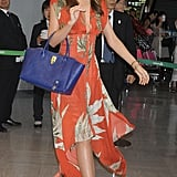 Miranda Kerr arrived at Narita International Airport in a mixture of colors and prints. She paired an orange Wes Gordon high-low dress with leopard Bionda Castana heels and a bright blue bag.
