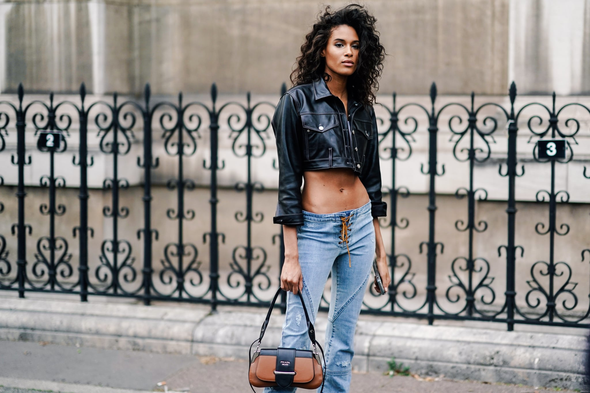 PARIS, FRANCE - FEBRUARY 28: Cindy Bruna wears a black leather crop jacket, blue lace up low waist jeans, a brown Prada bag, outside Redemption, during Paris Fashion Week Womenswear Fall/Winter 2019/2020, on February 28, 2019 in Paris, France. (Photo by Edward Berthelot/Getty Images)