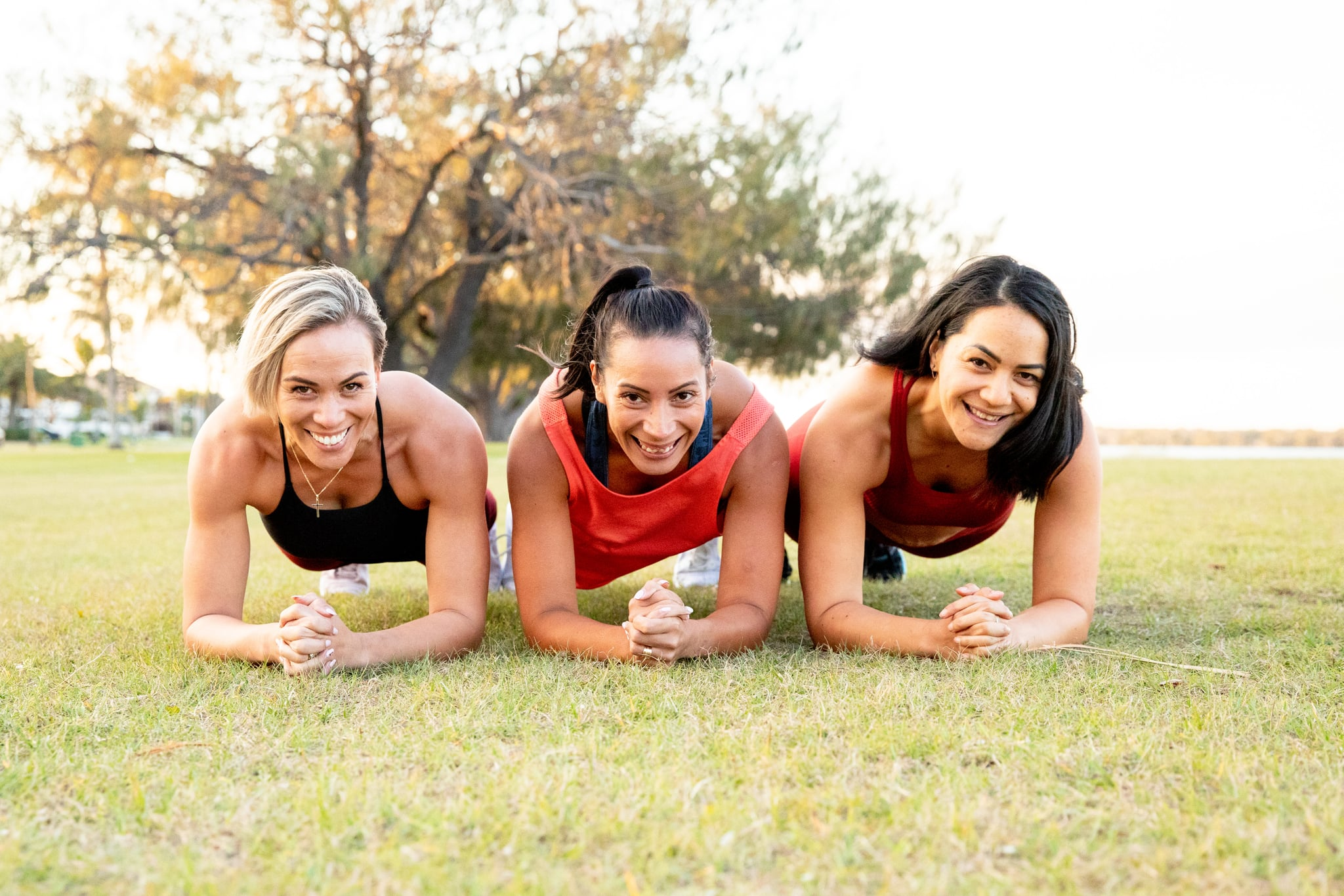 Three strong women working out together to keep fit, healthy and happy by the beach in active wear. Lifting weights, running and building core strength.