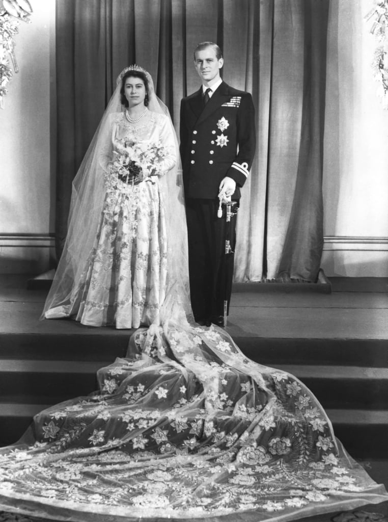 """The Queen's wedding gown was inspired by a painting. In Botticelli's """"Primavera,"""" the central figure wears a silky, draped ivory dress affixed with rose blossoms. This is the inspiration designer Sir Norman Hartnell took for Elizabeth's elaborate confection. The gown had a 15-foot train, and 10,000 pearls sourced from the United States.  Queen Elizabeth II saved ration cards to afford the fabric. Despite the gown's over-the-top inspiration, Elizabeth had to horde her ration cards in order to purchase the material needed for her wedding dress like any other woman at that time. The fabric she ended up with was created at Winterthur Silks Limited, using silk from Lullingstone Castle's Chinese silkworms.  All of her jewelry held sentimental value. The tiara she wore was one of her mother's, the diamond-encrusted Queen Mary Fringe, which was actually made for Queen Mary in 1919 from a diamond necklace given to her by Queen Victoria. Flowers were used sparingly as decorations. The tables at the reception were decorated with simple pink and white carnations donated by the British Carnation Society, since purse strings were tight after the war. Posies of myrtle and white heather from Balmoral were also given out as wedding favors."""