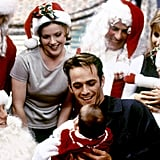 Luke Perry Holding a Baby Surrounded by Santas