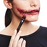 Paint on eye shadow and red lipstick until you get the bloody effect you want. Add more foundation around the edges to help cover any tissue that doesn't blend into the skin.
