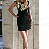 A prim, peplum-trimmed LBD got an edgy counter in a pair of leopard-print booties and a feathered statement necklace.