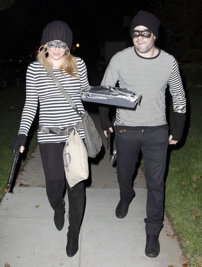 "Hilary Duff and her husband Mike Comrie wore matching cat burglar costumes last night as they headed to a Halloween party in LA. The parents-to-be brought along bags of fake money and Hilary even brandished a toy gun during their evening out. Hilary, who recently announced that their baby will be a boy, wasn't the only pregnant celeb to dress her bump in costume last night. Beyonce donned a ""bumble B"" suit for Kanye West's spooky NYC soiree, as well! Hilary's All Hallows' Eve celebration came after a busy first part of the month, most of which she spent promoting her new book, Devoted. Hilary headed to NYC and Minneapolis for signings before flying back home to the West Coast to pay a visit to The Ellen DeGeneres Show."