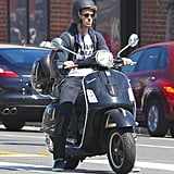 Andrew Garfield wore a backpack and black helmet riding his scooter around town.
