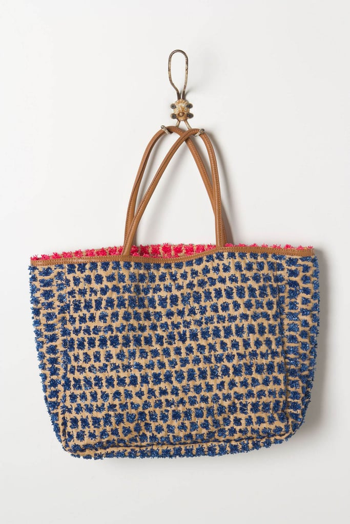 The raffia pom-pom details are a quirky play on traditional straw beach tote materials, and we love the pop of red peeking out, too. Anthropologie Pom Burst Tote ($68)