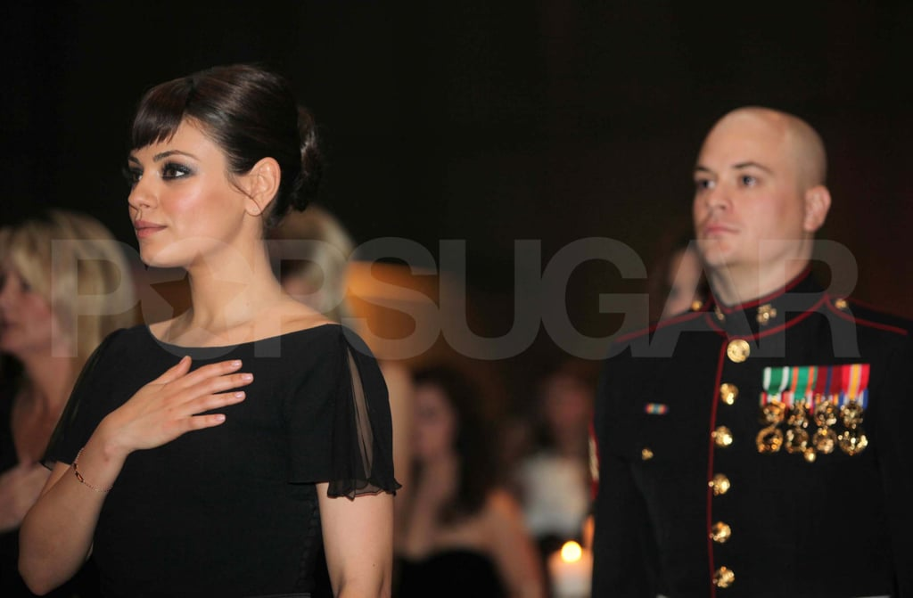 Mila Kunis does a saltue at the Marine Ball.