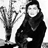 Coco Chanel, wearing pearl drop earrings with an embellished cap and fur coat in 1932.