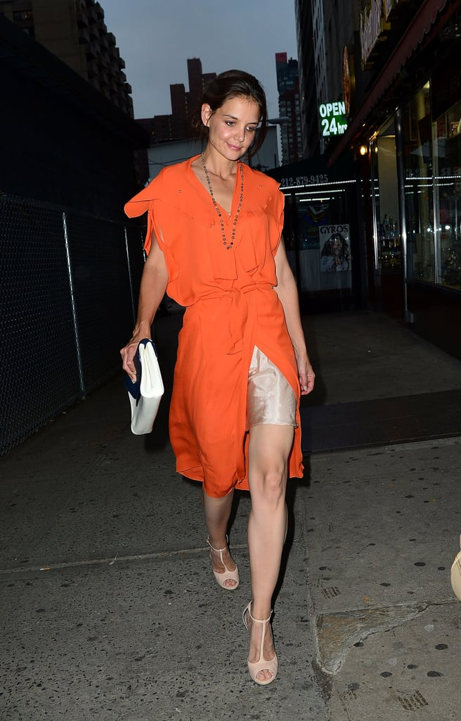 Katie Holmes stepped out in a bright orange chiffon shift dress, but didn't let the colour overwhelm. Instead, she let a nude slip peek through, paired the look with a sleek nude T-strap sandal, and finished it off with a blue and white clutch.