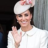 """أضافت كيت ومضة من الورديّ البارز على قبّعتها في حفل الاستقبال الذي أقيم بساحة """"غراند بلاس"""" في بلجيكا عام 2014."""